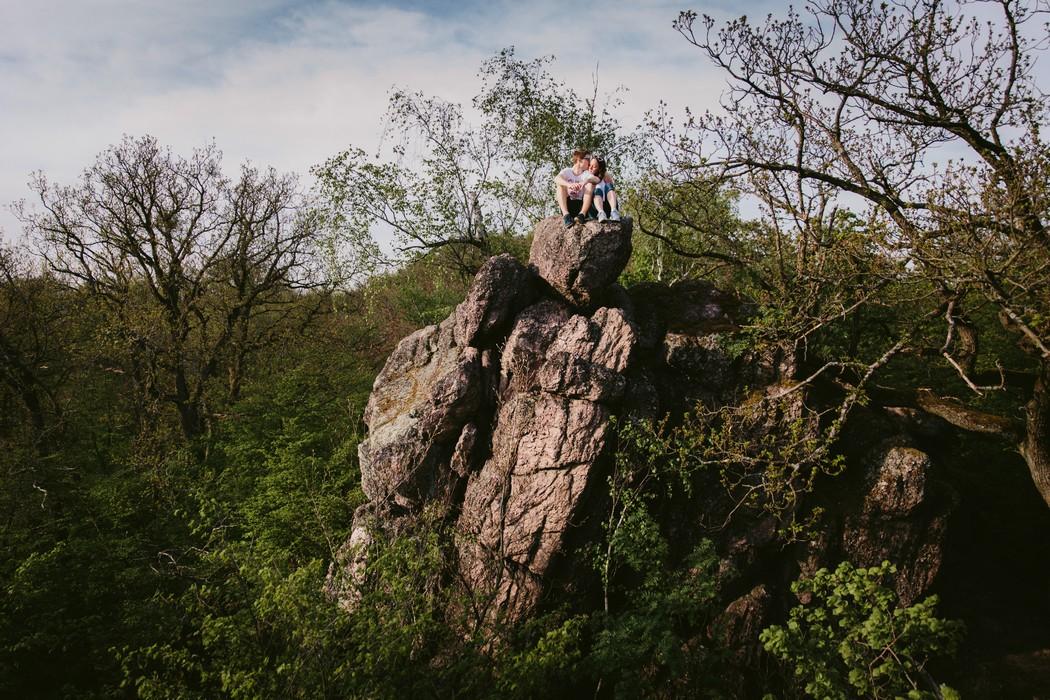 Snoubenci spolecne sedi na skale v Babim lomu.