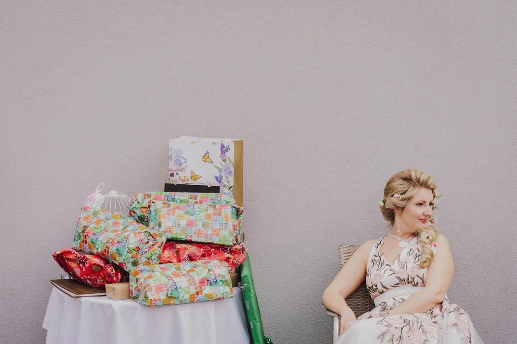 Nevesta sedi pri stole plnem svatebnich daru.