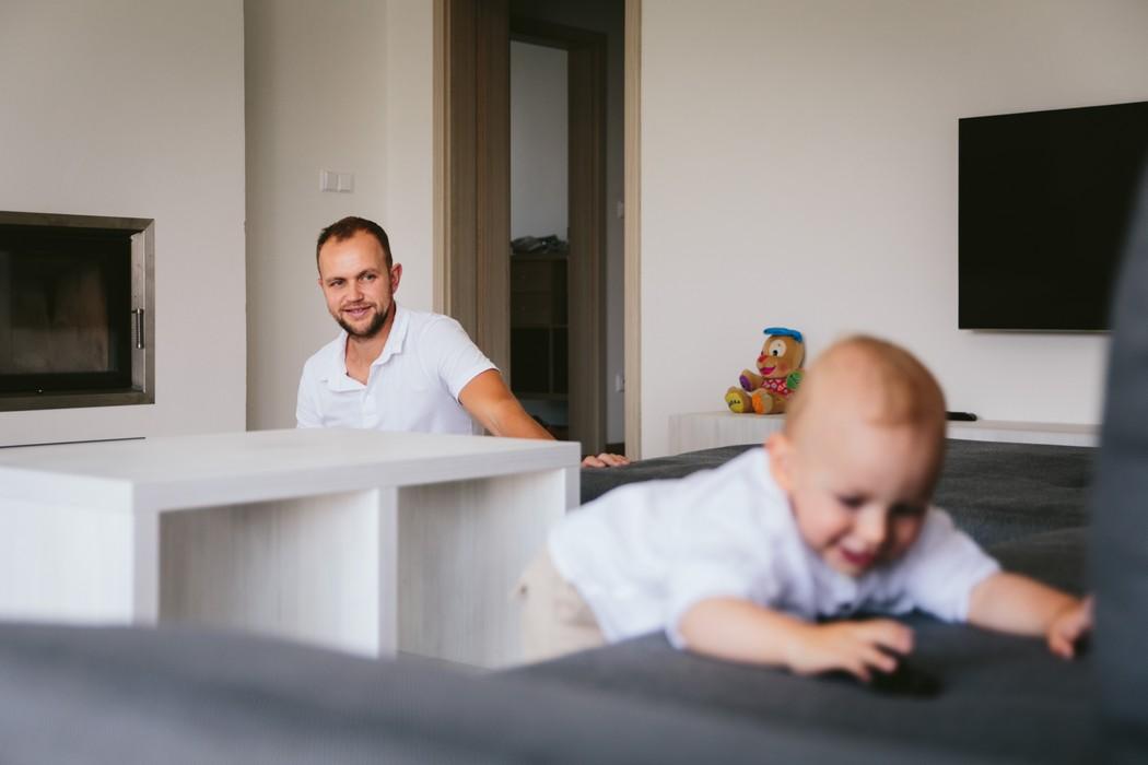 dítě se hraje a tatínek ho sleduje z povzdálí
