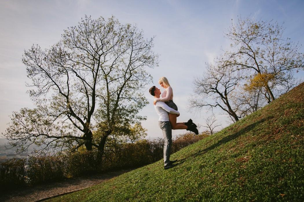 Snoubenci se objímají v parku v Brně