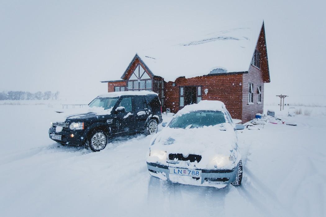 auta parkují před domem v zimě