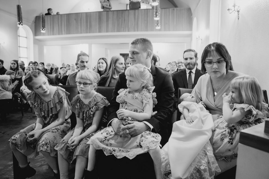 Rodina sedí v kostele před křtem