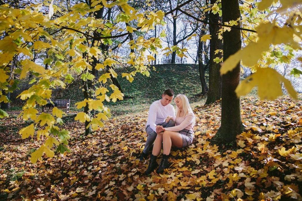 Průhled cez žluté listí na sedící snoubence