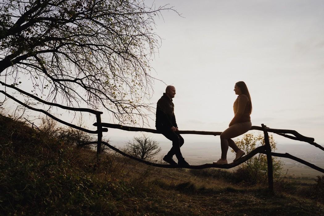 snoubenci sedící na plotě